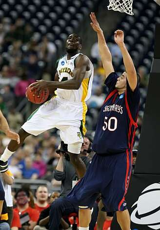 Quincy Acy of Baylor goes for a shot over Omar Samhan of St. Mary's in the first half of their NCAA Tournament game on Friday in Houston. Photo: George Bridges, MCT