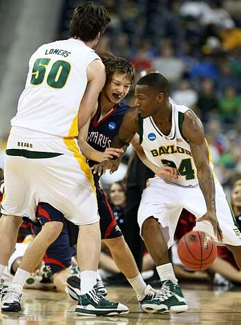 Josh Lomers of Baylor sets a pick for Matthew Dellavodova of St. Mary's as LaceDarius Dunn of Baylor drives  in the first half of their NCAA Tournament game on Friday in Houston. Photo: George Bridges, MCT