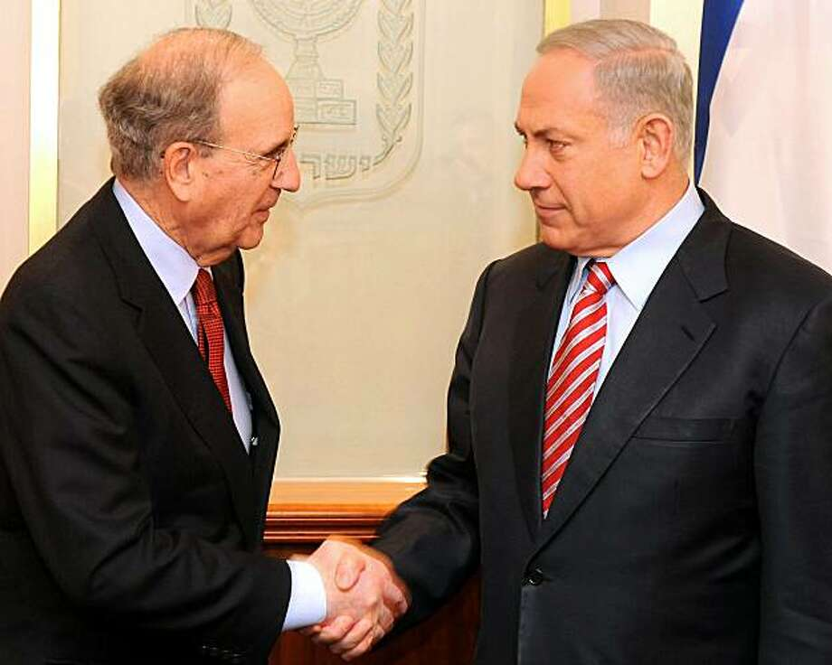 A handout picture released by the Israeli Government Press Office (GPO) shows US Middle East envoy George Mitchell (L) shaking hands with Israeli Prime Minister Benjamin Netanyahu during a meeting in Jerusalem on March 21, 2010. Netanyahu vowed there would be no halt to settlement building in east Jerusalem but said Israel was willing to widen the scope of planned indirect peace talks with the Palestinians. Photo: -, AFP/Getty Images