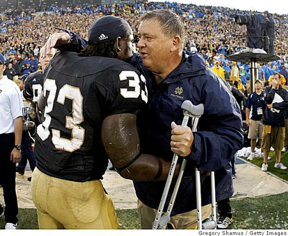 SOUTH BEND, IN - SEPTEMBER 13:  Head coach Charlie Weis of the Notre Dame Fighting Irish is congratulated by Robert Hughes #33 during the final seconds of their 35-17 victory over the Michigan Wolverines on September 13, 2008 at Notre Dame Stadium in South Bend, Indiana.  (Photo by Gregory Shamus/Getty Images) Photo: Gregory Shamus, Getty Images
