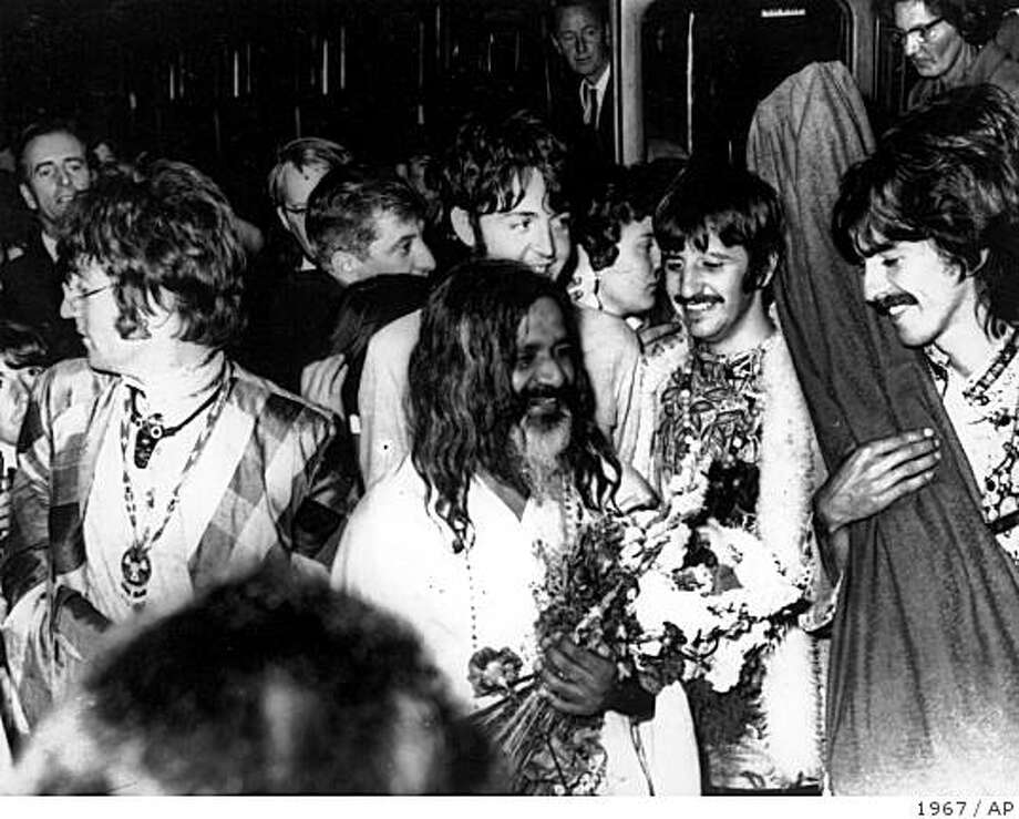 **FILE**The Beatles John Lennon, left, Paul McCartney, center background, Ringo Starr, second from right, and George Harrison, right, join the Maharishi Mahesh Yogi, center, as they arrive by train at Bangor, Wales, United Kingdom, to participate in a weekend of meditation in this file photo dated Aug. 26, 1967. Maharishi Mahesh Yogi, the Indian guru to the Beatles and millions of meditators, died late Tuesday, Feb. 5, 2008 at his home in the Dutch town of Vlodrop, a spokesman said. The Maharishi was believed to be 91. (AP Photo, File) Photo: 1967, AP