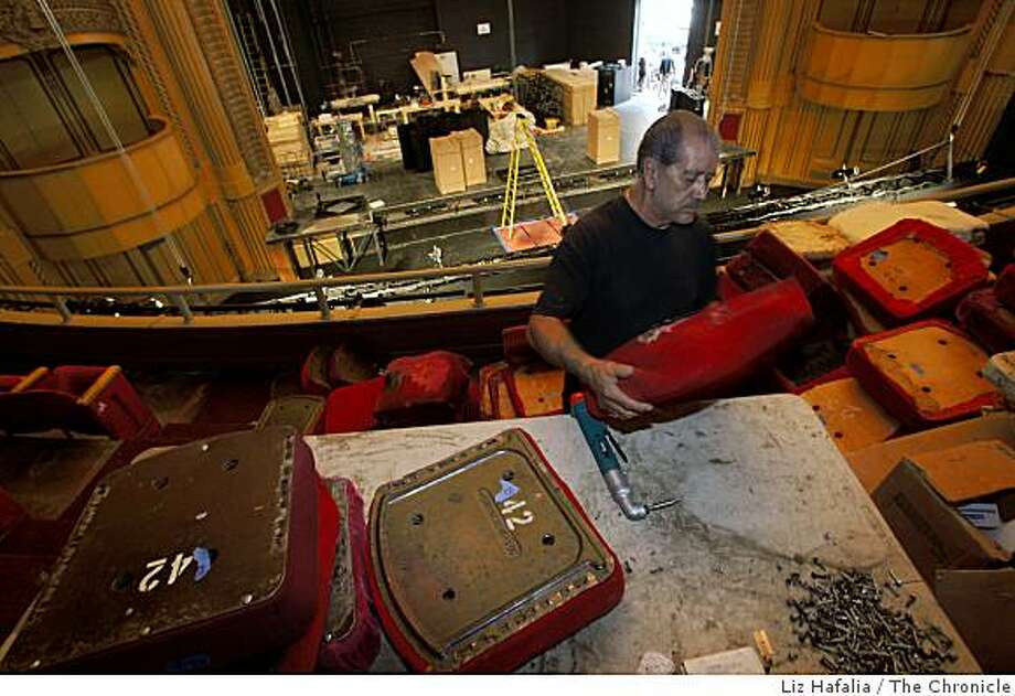 The Warfield theater in San Francisco, Calif., site of countless rock concerts, is being remodeled.    Francisco Rodriguez works on renovating mezzanine seats as he strips material from the seats where the sound board used to be on Monday, September 8, 2008. Photo: Liz Hafalia, The Chronicle