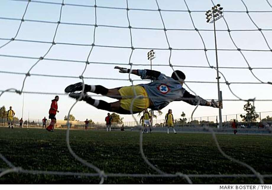 The goalie for team Olympo dives for a penalty kick during a recent match. In Santa Ana, Calif., more than 12,000 registered soccer players vie for space on just 29 city fields. Illustrates CALIF-SOCCER (category a) by Tony Barboza (c) 2008, Los Angeles Times. Moved Thursday, Sept. 4, 2008. (MUST CREDIT: Los Angeles Times photo by Mark Boster.) Photo: MARK BOSTER, TPN