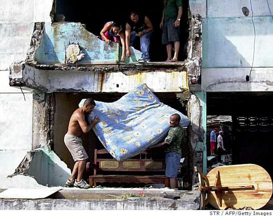 People in Baracoa recover some of their belongings from their destroyed houses, after the passage of Hurracane Ike on September 8, 2008. Cuba raised its hurricane alert level to maximum for the capital Havana as deadly hurracane Ike raged westward across the island towards the city of 2.2 million people, Cuban state television announced.  AFP PHOTO/STR (Photo credit should read STR/AFP/Getty Images) Photo: STR, AFP/Getty Images
