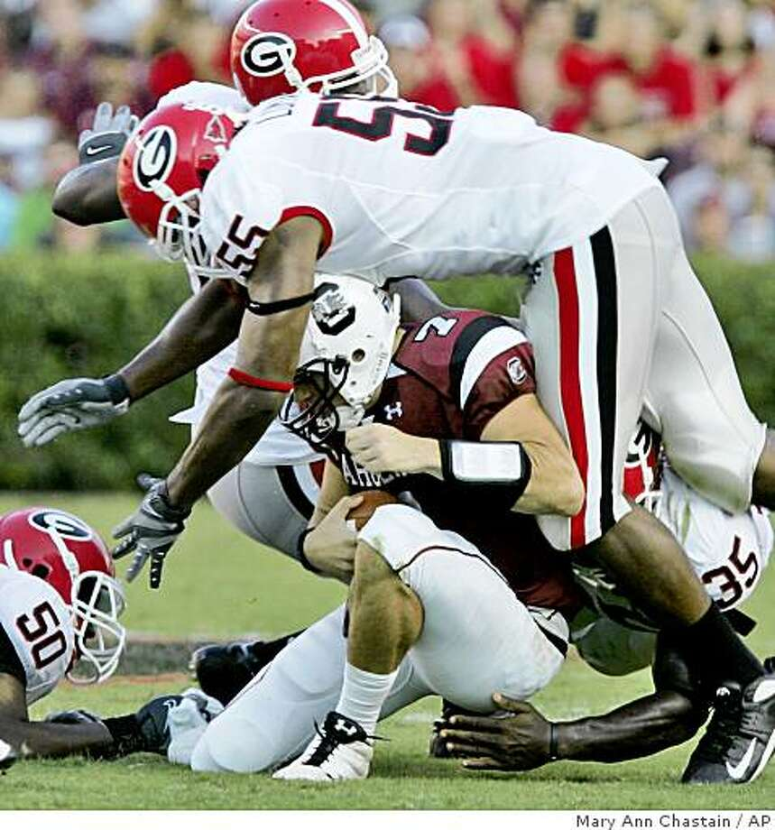 Georgia's Jeremy Lomax (55) falls over South Carolina's Chris Smelley (7) as he is sacked in the fourth quarter of an NCAA college football game Saturday, Sept. 13, 2008, at Wiliams Brice Stadium in Columbia, S.C. Georgia won14-7.(AP Photo/Mary Ann Chastain) Photo: Mary Ann Chastain, AP