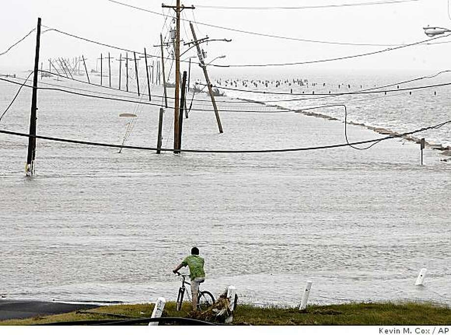 A lone man takes a closer look at what is left of the Texas City Dyke Saturday, Sept. 13, 2008 in Texas City, Texas. Howling ashore with 110 mph winds, Hurricane Ike ravaged the Texas coast Saturday, flooding thousands of homes and businesses, shattering windows in Houston's skyscrapers and knocking out power to millions of people. (AP Photo/The Galveston County Daily News, Kevin M. Cox) ** MANDATORY CREDIT, NO SALES, MAGS OUT, TV OUT ** Photo: Kevin M. Cox, AP
