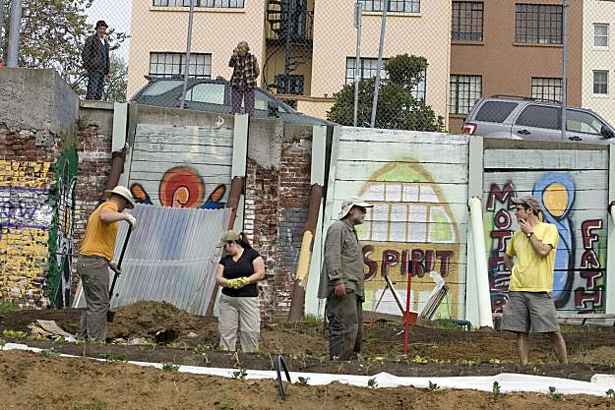 Curious neighbors peek through the fence above as, from left, Jim Sweeney, Peta Poole,