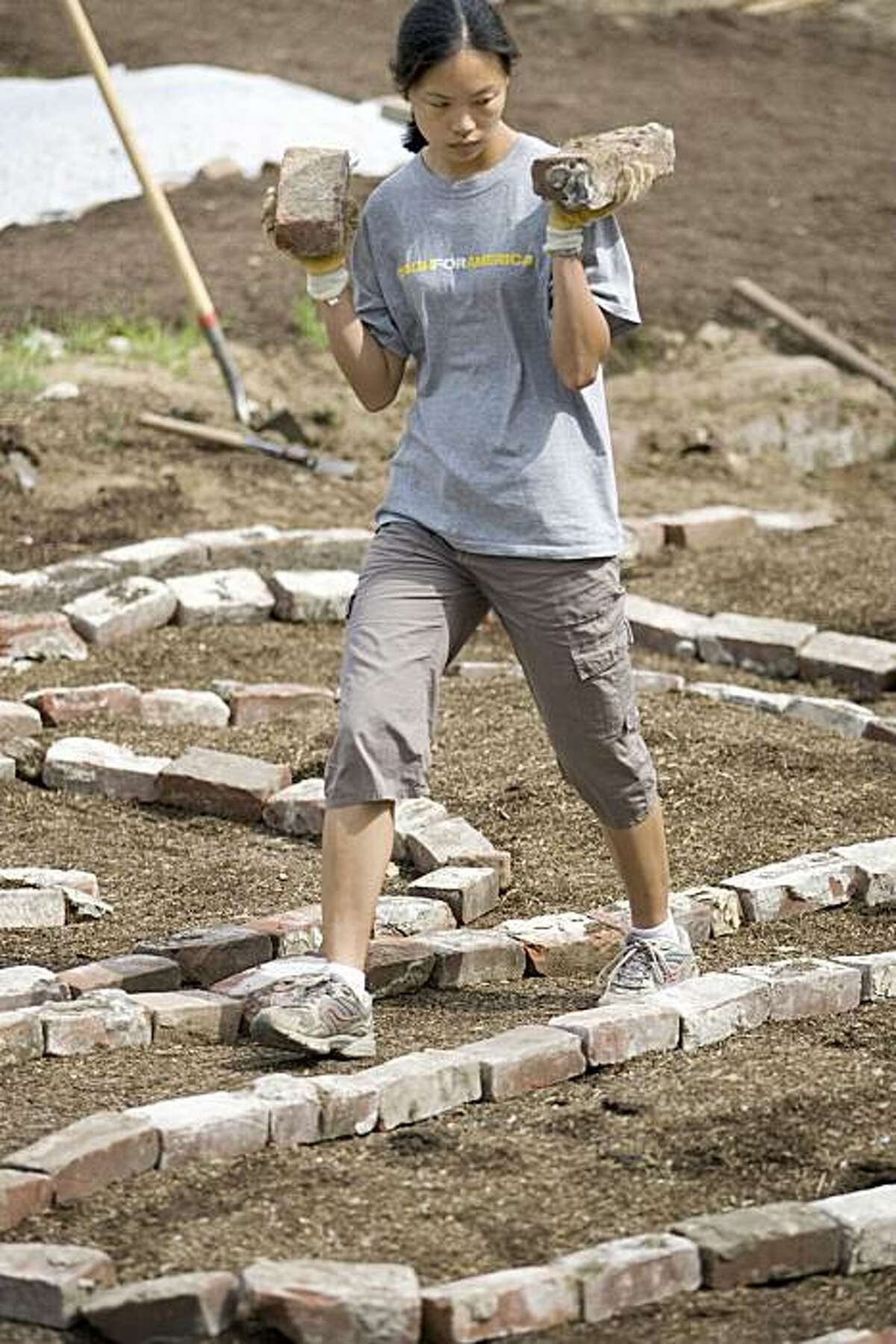 Wendy Landerholm who works with the organization Urban Sprouts, replaces the stone outline of a Labyrinth / herb garden with bricks while volunteering at an urban farm at the corner of Gough and Eddy in San Francisco, Calif. on Saturday, March 20, 2010. Kat Wade / Special to the Chronicle