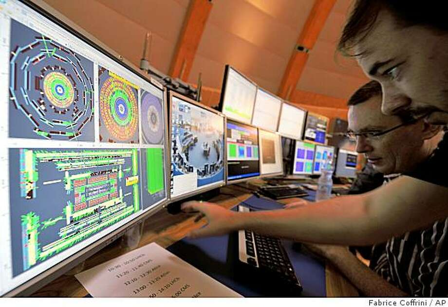 European Center for Nuclear Research (CERN) scientists control computer screens showing traces on Atlas experiment of the first protons injected in the Large Hadron Collider (LHC) during its switch on operation at the Cern's press center on Wednesday, Sept. 10, 2008 near Geneva, Switzerland. Scientists fired a first beam of protons around a 27-kilometer (17mile) tunnel housing the Large Hadron Collider (LHC). They hope to recreate conditions just after the so-called Big Bang. The international group of scientists plan to smash particles together to create, on a small-scale, re-enactments of the Big Bang. (AP Photo/Fabrice Coffrini, Pool) Photo: Fabrice Coffrini, AP