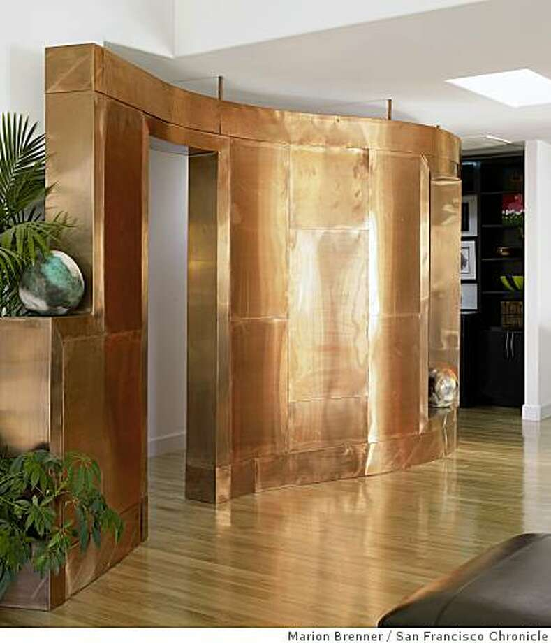 Copper interior wall in Barker's home. Pat Barker�s modernist-ranch house in San Lorenzo.  She created a modern loft-style living space in a small house riddled with small rooms, walls and little natural light. Photo: Marion Brenner, San Francisco Chronicle