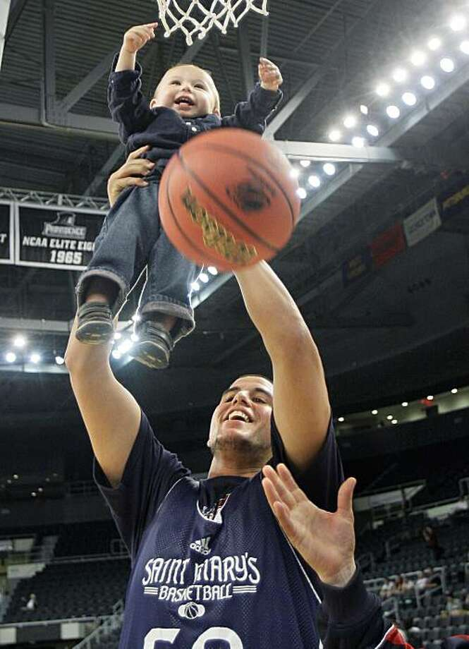 Omar Samhan of Saint Mary's lifts 18-month-old Rocco Smith for a dunk during NCAA college basketball practice in Providence, R.I. Wednesday, March 17, 2010. Saint Mary's will face Richmond in a first-round South Regional game on Thursday. Photo: Elise Amendola, AP