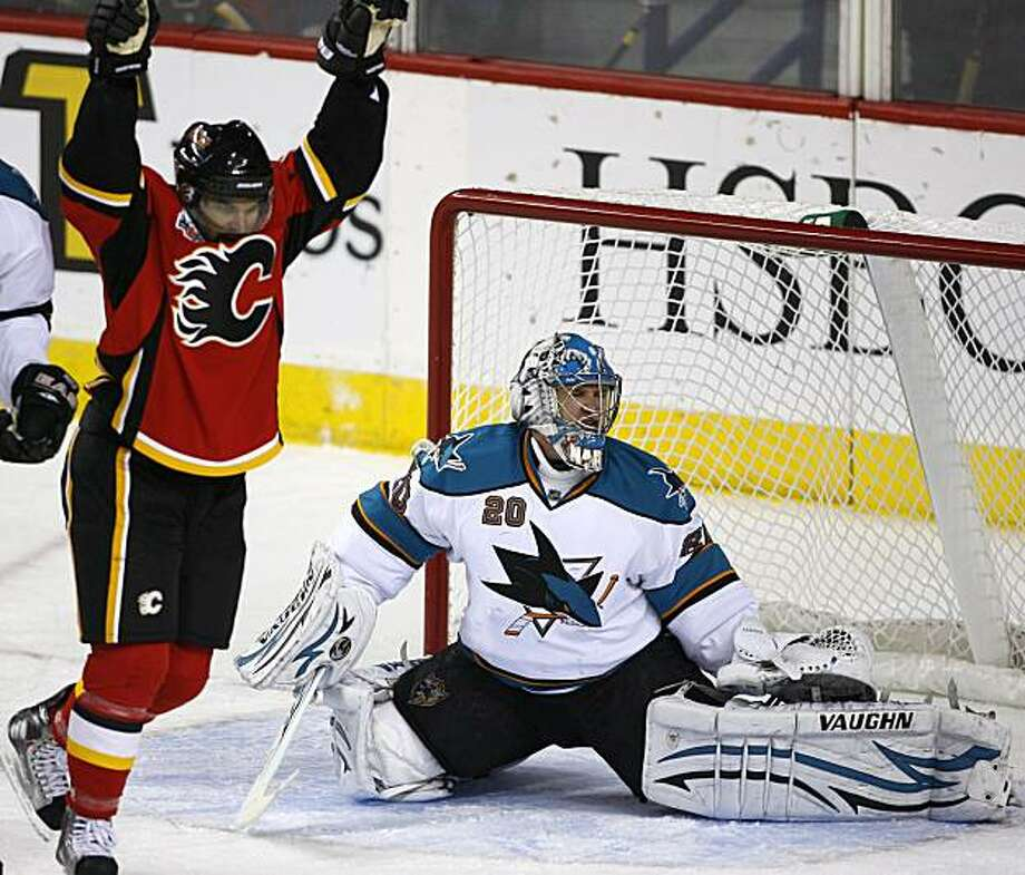 San Jose Sharks' goalie Evgeni Nabokov, from Kazakastan, reacts after a goal by Calgary Flames' Nigel Dawes, left, during second period NHL hockey action in Calgary on Friday March 19, 2010. Photo: Larry MacDougal, AP