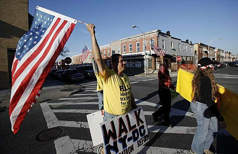 Saul Linares, left, waves an American flag after arriving at a church in Baltimore, Thursday, March 18, 2010, after walking the past six days from Hempstead, NY. Linares, a factory worker, will join other immigrants, most of them undocumented Hispanics, in Washington, D.C., for a Sunday march to dramatize their pleas for immigration reform. Photo: Rob Carr, AP