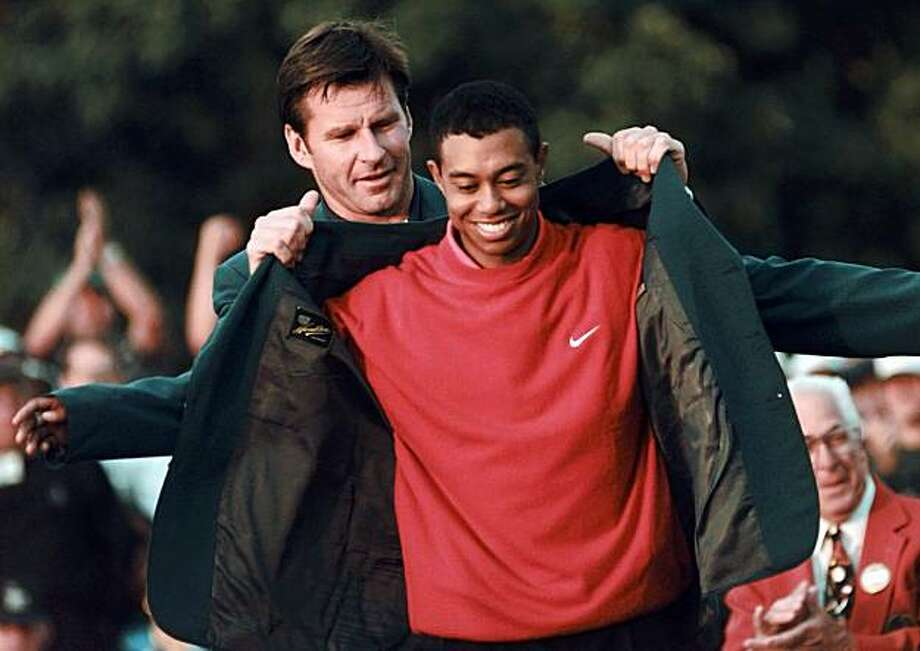 FILE - In this April 13, 1997, file photo, Masters champion Tiger Woods receives his green jacket from the previous year's winner Nick Faldo, rear, at the Augusta National Golf Club in Augusta, Ga. In a statement Tuesday, March 16, 2010, Woods said he will play at Augusta National after a four-month hiatus because of a sex scandal. The Masters begins on April 8. Photo: Dave Martin, AP