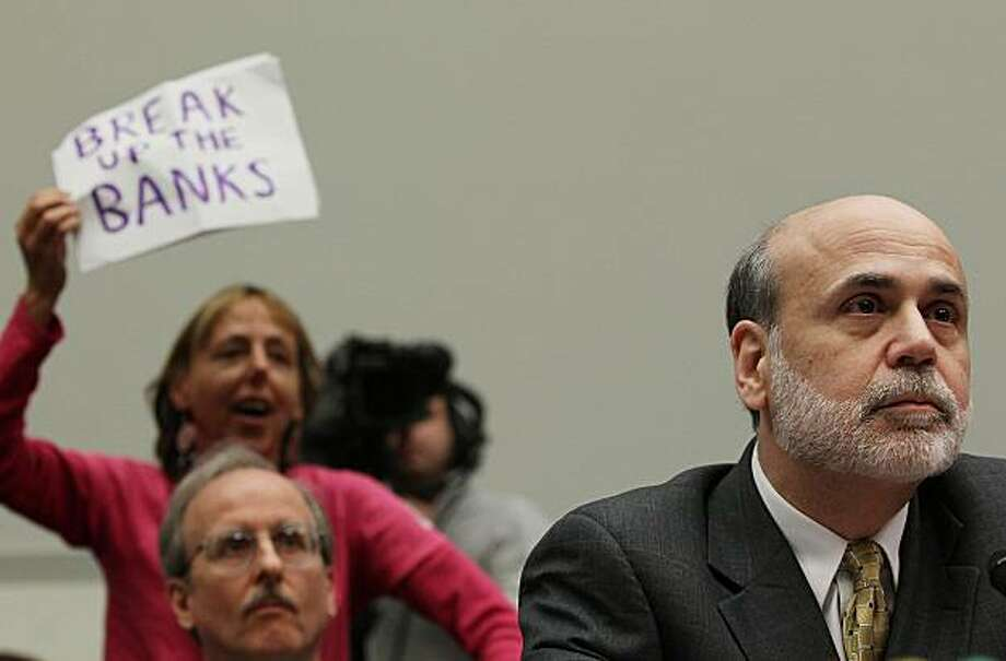 WASHINGTON - MARCH 17: Code Pink member Medea Benjamin (L) holds up a sign while Federal Reserve Board Chairman Ben Bernanke testifies during a House Financial Services Committee hearing on Capitol Hill on March 16, 2010 in Washington, DC. The committee is examining the link between Federal Reserve supervision and monetary Policy. Photo: Mark Wilson, Getty Images