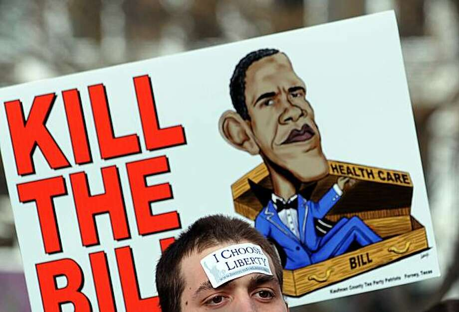 "Participants display placards during a demonstration organized by the American Grass Roots Coalition and the Tea Party Express in Washington, DC, on March 16, 2010 in opposition to the health care reform bill. US President Barack Obama called for ""courage"" from Democratic lawmakers unnerved by looming final votes on his historic health care plan in a pivotal political week that may shape his presidency. Photo: Jewel Samad, AFP/Getty Images"