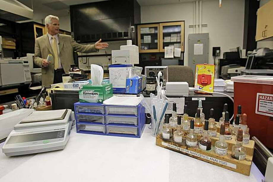 """Lab director Jim Mudge shows criminalist Deborah Madden's work station at the police crime lab in San Francisco on Wednesday, March 10, 2010. Madden is accused of stealing cocaine last year that was used as criminal evidence by prosecutors. San FranciscoPublic Defender Jeff Adachi said the allegations could affect """"hundreds if potentially thousands of cases."""" Photo: Marcio Jose Sanchez, AP"""