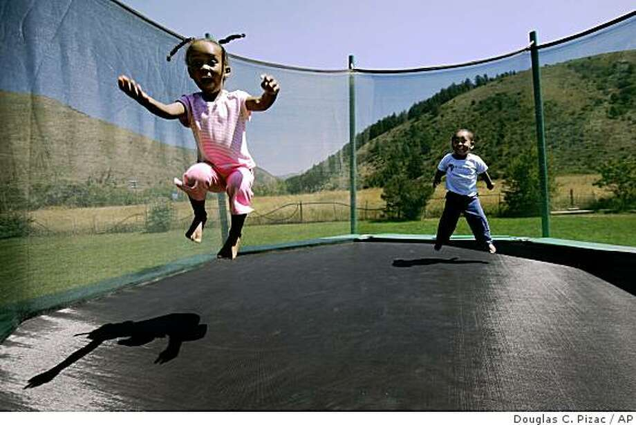 Belane, left, and Solomon, who have HIV, play on a trampoline at the home of their adoptive parents' Erin and Joshua Henderson, Monday, Aug. 11, 2008, in western Wyoming.  (AP Photo/Douglas C. Pizac) Photo: Douglas C. Pizac, AP