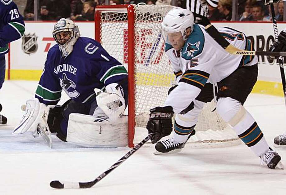 San Jose Sharks' Dany Heatley, right, carries the puck around the net as Vancouver Canucks' Roberto Luongo watches during an NHL hockey game in Vancouver, British Columbia, on Thursday, March 18, 2010. Photo: Darryl Dyck, AP