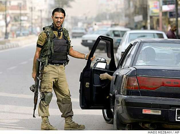 A 'Sons of Iraq' volunteer stands guard at a checkpoint in the Azamiyah neighborhood in north Baghdad, Iraq Monday, Sept. 8, 2008. Iraq's Shiite-led government promised Monday to continue paying salaries of thousands of mostly Sunnis who turned against al-Qaida but said the U.S. figure on their numbers was too high. (AP Photo/Hadi Mizban) Photo: HADI MIZBAN, AP