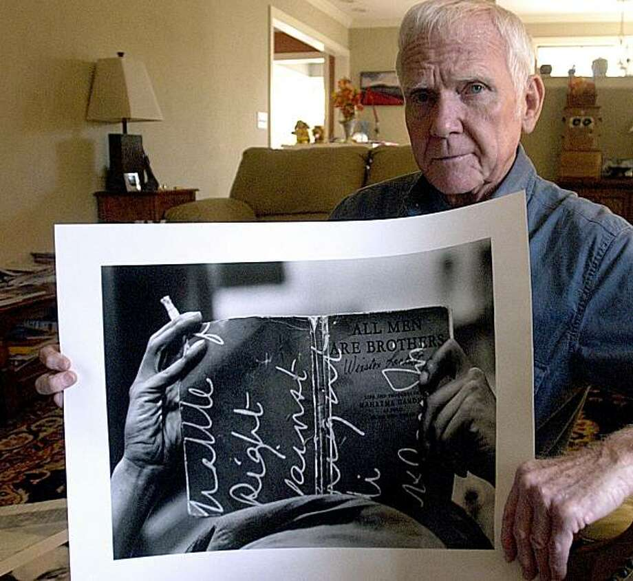 ** REMOVES REFERENCE OF PULITZER PRIZE ** This November 2004 photo shows photographer Charles Moore holding one of his photographs. Moore, a photographer who chronicled the civil rights movement, has died. John Edgley of Edgley Cremation Services in West Palm Beach, Fla., confirmed that Moore died Thursday, March 11, 2010. He was 79. (AP Photo/TimesDaily, Jim Hannon) MANDATORY CREDIT. Photo: Jim Hannon, AP