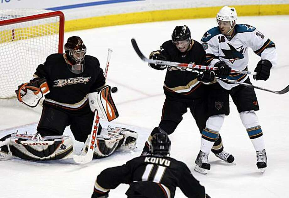 Anaheim Ducks goalie Jonas Hiller, of Switzerland, makes a save in the third period as teammate Lubomir Visnovsky and San Jose Sharks' Devin Setoguchi work for position in an NHL hockey game in Anaheim, Calif., on Sunday, March 14, 2010. Photo: Christine Cotter, AP