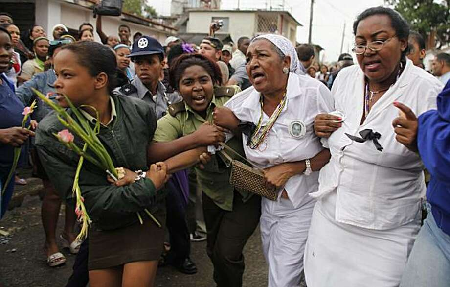 """Members of the """"Ladies in White"""", a group of female dissidents, are removed from the street by security agents during a protest in Havana, Wednesday, March 17, 2010. Cuban security agents have prevented the group of female dissidents from marching on theoutskirts of the capital to demand the release of their jailed husbands and sons, physically removing them when they lay down in the street in protest. Photo: Javier Galeano, AP"""