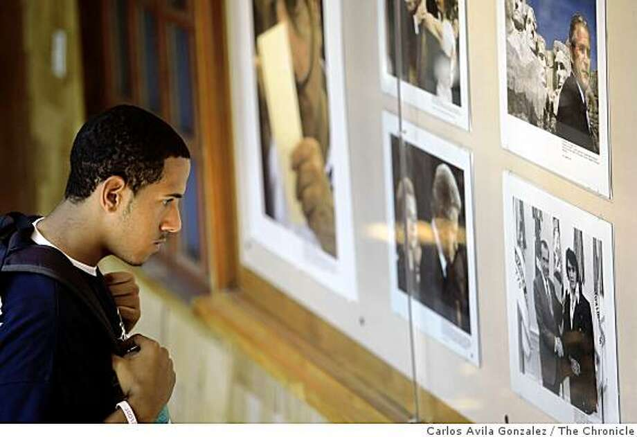Tyler Turner, an economics major at UC Berkeley, looks over the photos that are on display at North Gate Hall at UC Berkeley. Photo: Carlos Avila Gonzalez, The Chronicle
