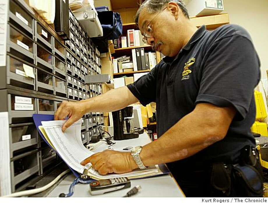San Francisco Police Sergeant Wayne Hom's job is to extract as much data from anything that stores information such as cell phones, computers and Blackberries. He starts by looking up the phone in a master list by brand. Photo: Kurt Rogers, The Chronicle