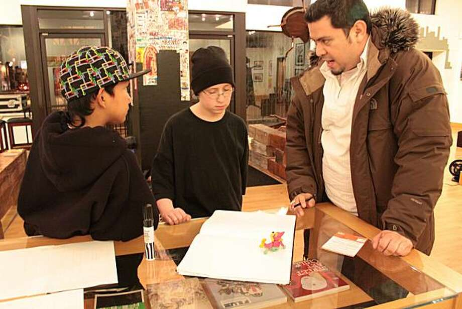 Left to right, Josh Ramos, Maher Jakub and Josue Rojas, who works with Youth Outlook, review artwork at 1:AM Gallery in San Francisco. Josh and Maher worked on a census themed mural in the city. Photo: Courtesy Photo