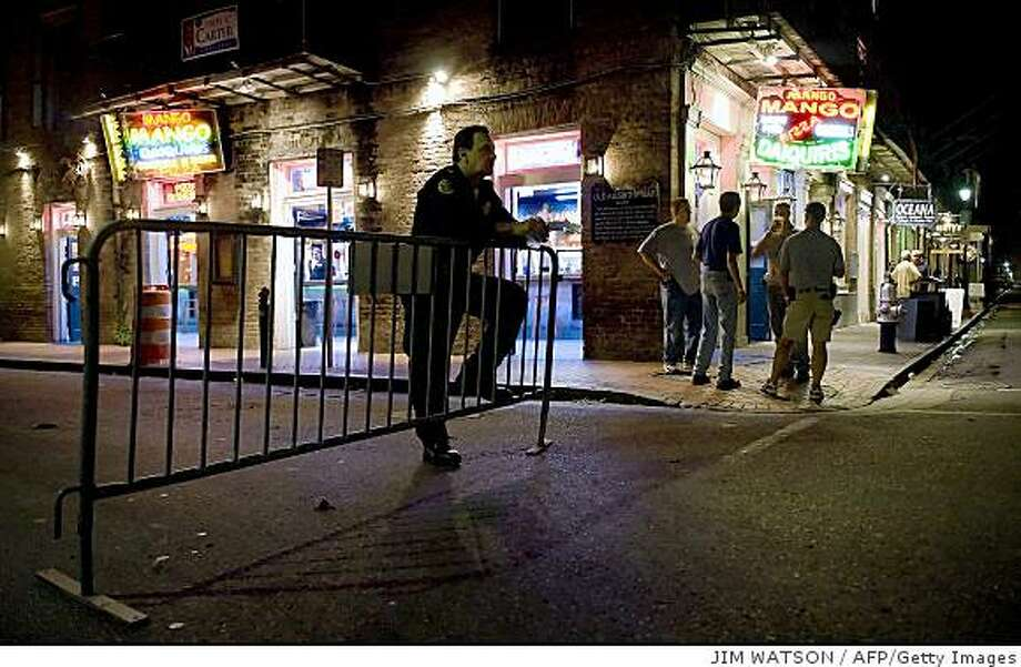 A New Orleans police officer stands guard as patron have a drink on Bourbon Street in the French Quarter of New Orleans, Louisiana, September 3, 2008 as residents slowly make their way back to their homes and businesses after Hurricane Gustav.         AFP PHOTO/Jim WATSON (Photo credit should read JIM WATSON/AFP/Getty Images) Photo: JIM WATSON, AFP/Getty Images