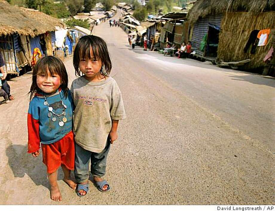 A pair of ethnic Hmong refugee children from Laos smile proudly as they pose for photographs at a refugee shelter in the Huay Nam Khao, Thailand Monday, Feb. 5, 2007. More than 8,000 illegal refugees are living at the camp with more than 25 new babies being born each month. Photo: David Longstreath, AP