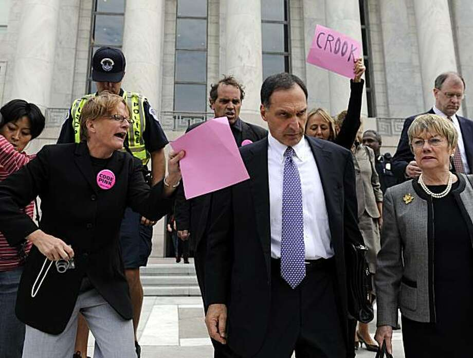 FILE - In this Oct. 6, 2008 file photo, Lehman Brothers Holdings Inc. Chief Executive Richard S. Fuld Jr., front center, is heckled by protesters as he leaves Capitol Hill in Washington after testify before the House Oversight and Government Reform Committee on the collapse of Lehman Brothers. A report by U.S. bankruptcy-court examiner faults Lehman Brothers  executives and auditor Ernst & Young for serious lapses that led to the largest bankruptcy in U.S. history. Will former CEO Richard Fuld be held accountable? Photo: Susan Walsh, AP