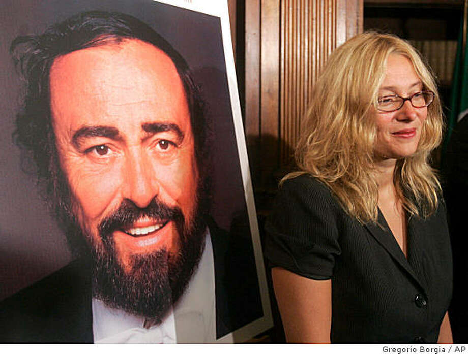 Nicoletta Mantovani poses next to the picture of her husband, late Italian Tenor Luciano Pavarotti, at  a press conference at Rome's Culture Ministry building, Friday, Sept. 5, 2008, to commemorate the first anniversary of his death. Pavarotti died in Modena, Sept. 6, 2007. Photo: Gregorio Borgia, AP