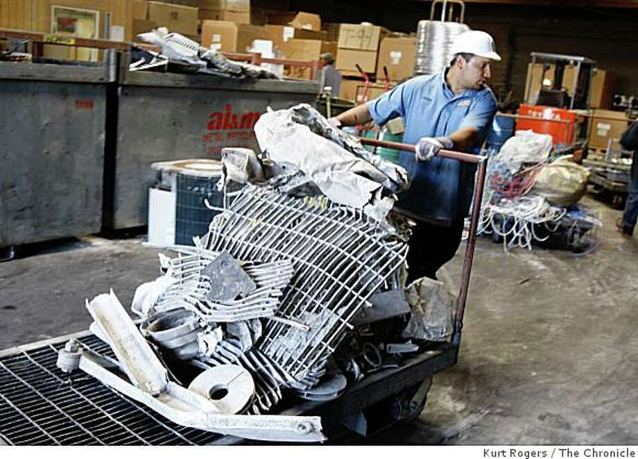 Adrian Zamora 21 polls a cart of metal to be recycled the pieces will be put into bens of the same kind then will be shipped out. on Tuesday, Sept, 2  2008 in San Leandro , Calif Photo: Kurt Rogers, The Chronicle