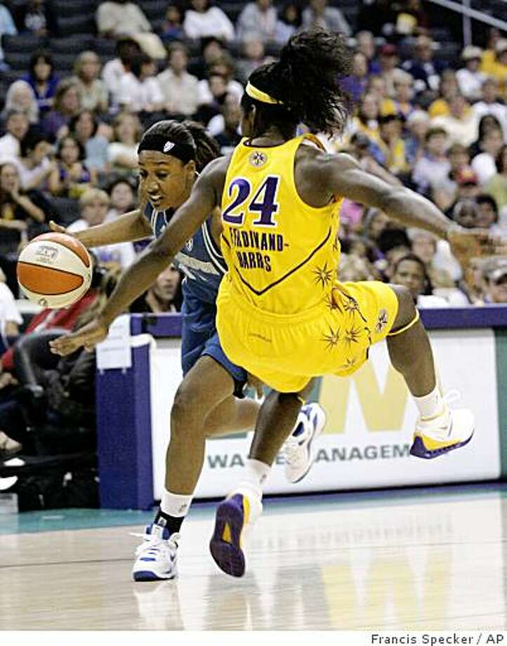 Minnesota Lynx's Candice Wiggins, left, knocks over Los Angeles Sparks' Marie Ferdinand-Haris on a charging foul in the first half of a WNBA basketball game in Los Angeles on Monday, Sept. 1, 2008. (AP Photo/Francis Specker) Photo: Francis Specker, AP