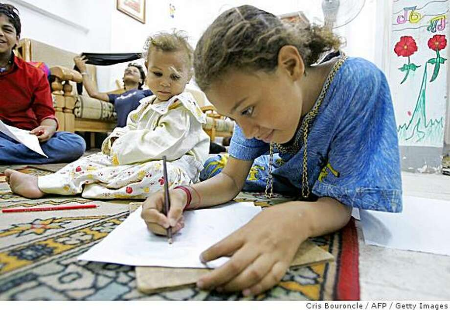 In a file picture taken August 26, 2004, 13-year-old Amany draws on the floor as her three-year-old sister Farha sits close by in the lounge of an all-girls rehabilitation shelter called 'Hope Village' in Cairo. The organization has eleven shelters for homeless boys and girls up to 21 years of age, attempting to keep them off the streets away from illegal child labor and prostitution, in this city of over 15 million inhabitants. The UN children's agency UNICEF estimates that 2.7 million aged between six and 14 in Egypt are working children. Photo: Cris Bouroncle, AFP / Getty Images
