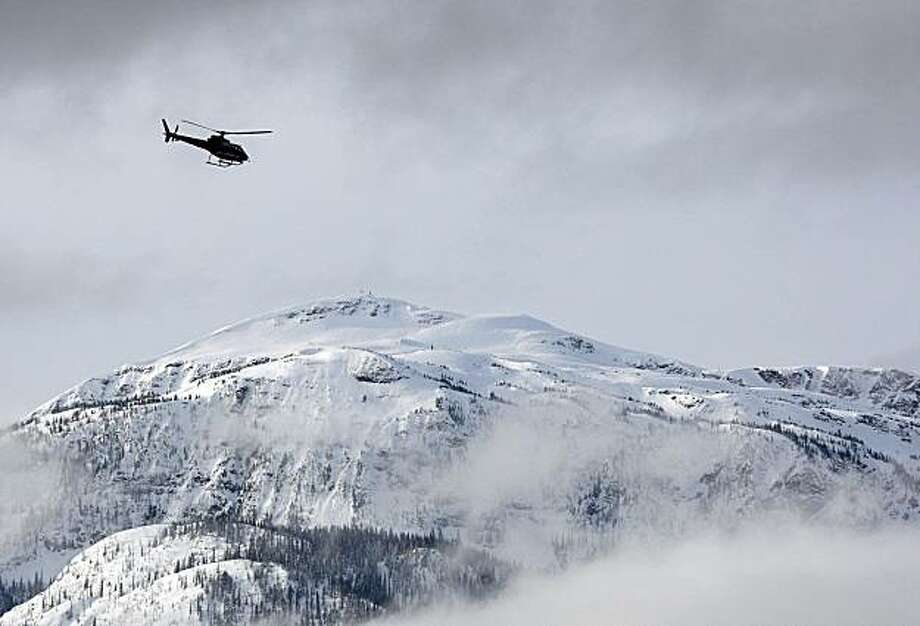 A search and rescue helicopter heads toward the area where a large avalanche struck near Revelstoke, British Columbia, Sunday, March 14, 2010. The avalanche struck an informal snowmobile rally Saturday in Canada's Rocky Mountains, killing at least three people and leaving an unknown number missing. Rescuers resumed scouring remote Boulder Mountain at daybreak Sunday after halting the search overnight. Police also conducted a door-to-door search of hotel rooms early Sunday to piece together how many peoplewere missing from the Big Iron Shoot Out rally. Photo: Jeff McIntosh, AP