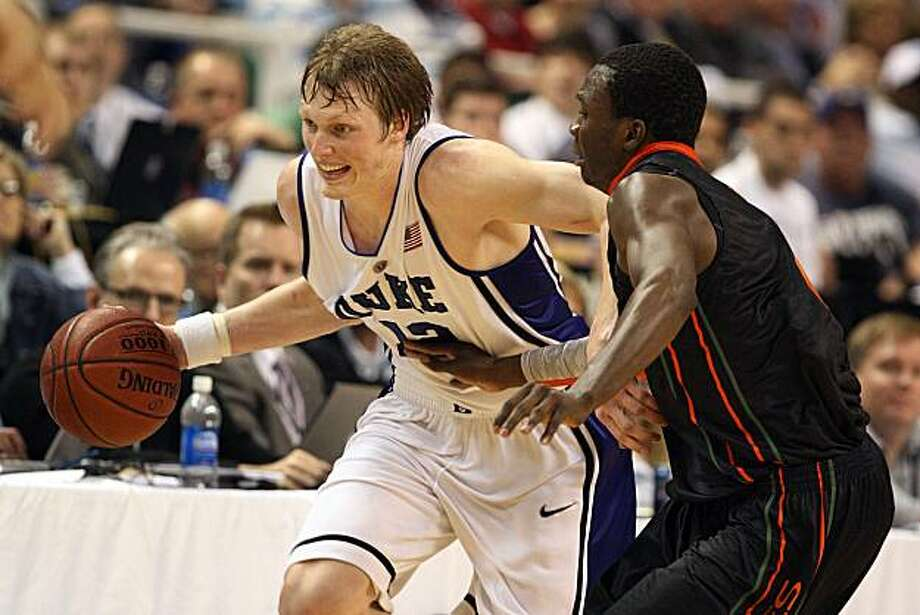 Duke's Kyle Singler (12) races up court with the ball while guarded by Miami's Garrius Adams (25) during game action in the ACC Men's Basketball Tournament at Greensboro Coliseum in Greensboro, North Carolina, Saturday, March 13, 2010. Duke defeated Miami, 77-74. (Chuck Liddy/Raleigh News & Observer/MCT) Photo: Chuck Liddy, MCT