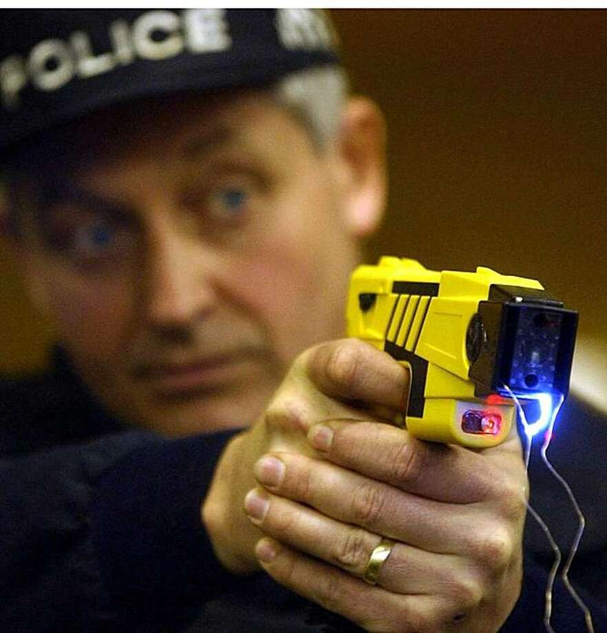 """This April 17, 2003 file photo shows a British policeman demonstrating a new stun gun.  Electric stun guns are to be authorised for police firearms officers across England and Wales following a successful trial, it was announced Wednesday Sept. 15, 2004.  Britain'sHome Secretary David Blunkett said scientific evaluations had shown the Taser guns had a """"very low"""" risk of fatality.  The American-manufactured weapons have been under controlled testing by five police forces since April last year as a less lethal alternative to conventional firearms. Photo: AP"""
