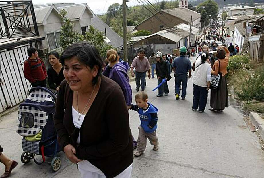 People walk up a hill following an aftershock in Constitucion, Chile, Thursday, March 11, 2010. The strongest aftershock since the Feb. 27 earthquake rocked the country as President Sebastian Pinera was sworn into office. Pinera urged coastal residents tomove to higher ground. Photo: Fernando Vergara, AP