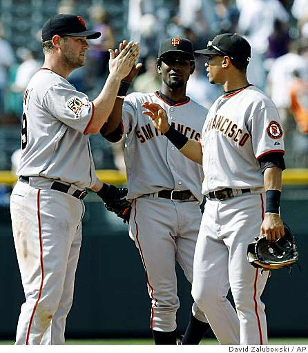 San Francisco Giants third baseman Scott McClain, left, is congratulated by second baseman Eugenio Velez, center, and shortstop Emmanuel Burriss after the Giants' 9-2 victory over the Colorado Rockies in a baseball game in Denver on Wednesday, Sept. 3, 2008. McClain collected three hits and drove in three runs to lead the Giants to the win. (AP Photo/David Zalubowski)
