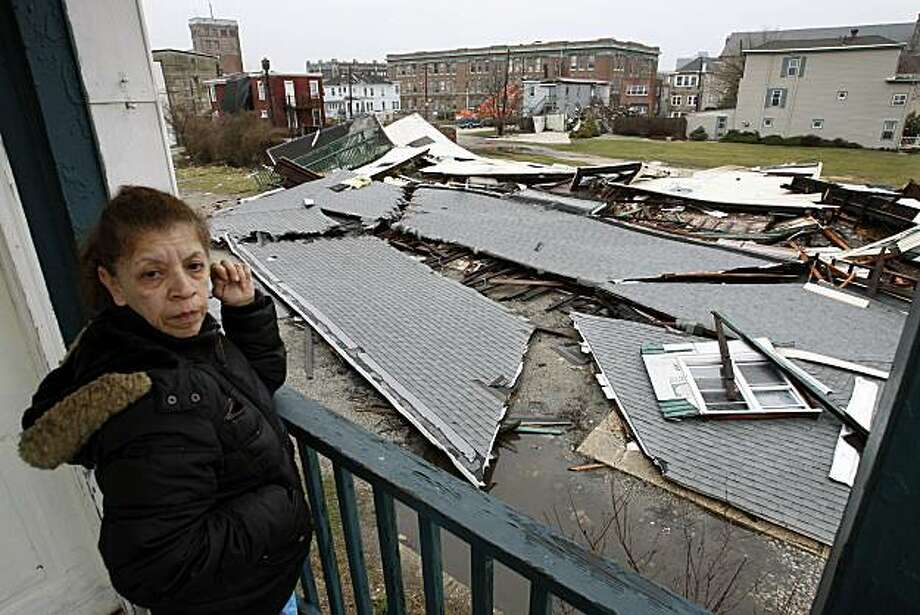 Iris Solano stands on the porch of her home overlooking the debris of her neighbor's house that collapsed in a storm that pounded the region over the weekend,  Sunday, March 14, 2010, in Atlantic City, N.J. Photo: Mel Evans, AP