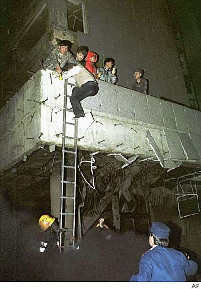 Chinese embassy staffers flee the Chinese embassy in Belgrade after it was reportedly hit by NATO cruise missiles early Saturday, May 8, 1999. The Yugoslav foreign ministry spokesman said some Chinese were killed when the embassy was hit in raids that plunged much of the city in darkness. In Beijing, China's official Xinhua News Agency reported five people were injured, at least one seriously, and three were missing. (AP PHOTO / str) YUGOSLAVIA OUT COMMERCIAL ONLINE OUT Photo: STR, AP