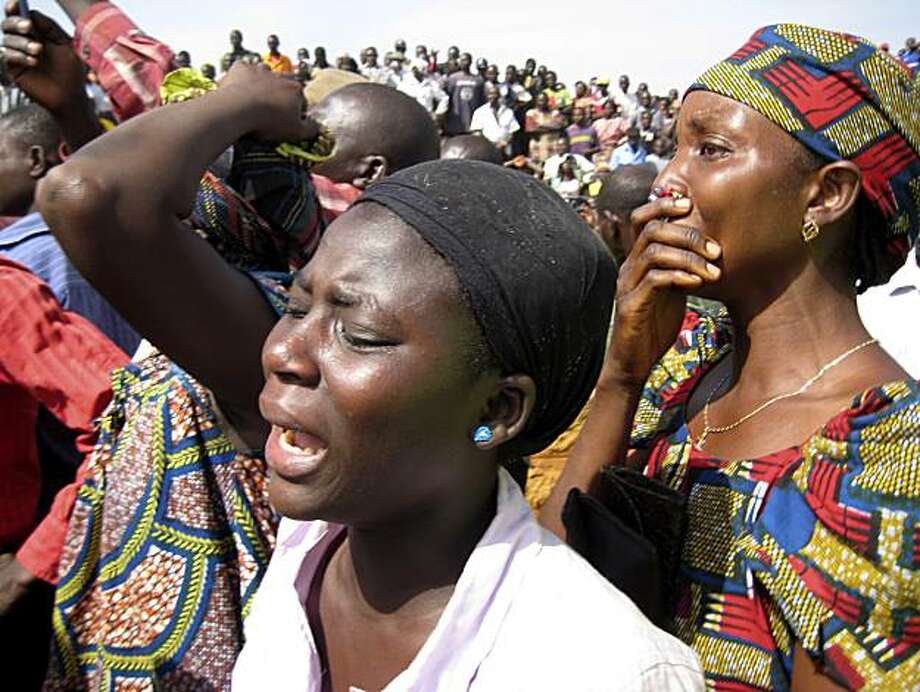 Unidentified women react to the sight of dead bodies in Dogo Nahwa, Nigeria, Monday, March 8, 2010. More than 200 people, most of them Christians, were slaughtered on Sunday in central Nigeria, according to residents, aid groups and journalists. The localgovernment gave a figure more than twice that amount, but offered no casualty list or other information to substantiate it. Photo: Jon Gambrell, AP