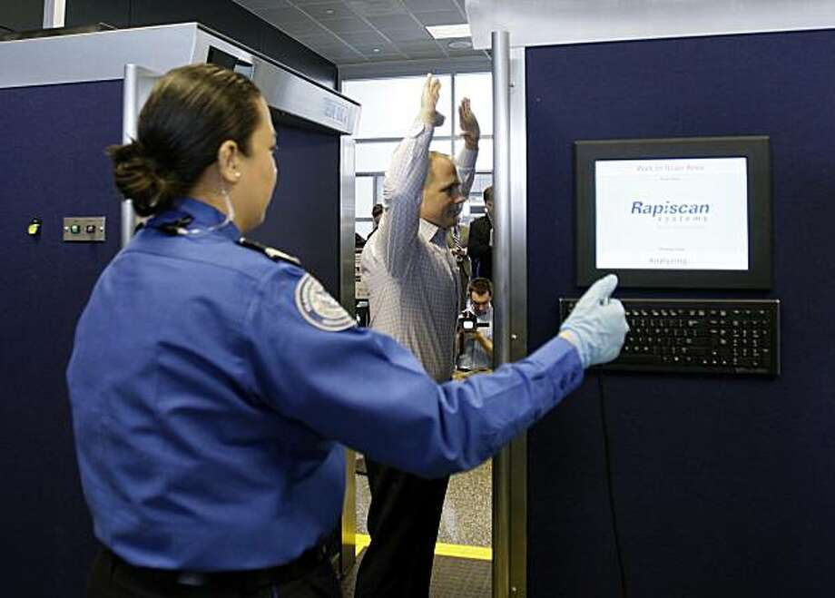 Transportation Security Administration employee John Carter demonstrates the stance in an advanced image technology unit as TSA supervisory officer Diana Hernandez operates the machine at Boston Logan International Airport, Friday, March 5, 2010, in Boston. Photo: Mary Schwalm, AP