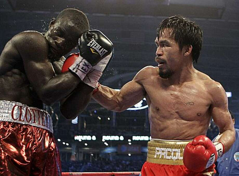 Manny Pacquiao, right, of the Philippines, lands a right to Joshua Clottey, from Ghana, during their WBO boxing welterweight title fight in Cowboys Stadium in Arlington, Texas, Saturday, March 13, 2010. Photo: David J. Phillip, AP