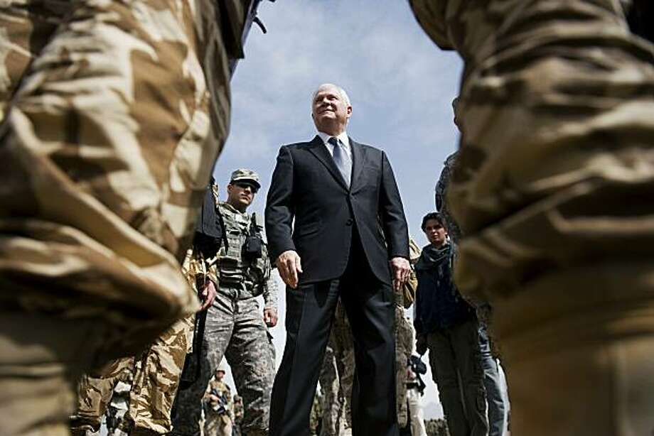 U.S. Defense Secretary Robert Gates, center, inspects troops as he tours the training grounds of Camp Blackhorse in Kabul, Afghanistan, on Wednesday, March 10, 2010. Gates raised the possibility Wednesday that some of the U.S. forces involved in the Afghanistan surge could leave the country before President Barack Obama's announced July 2011 date to begin withdrawal. Photo: Jim Watson, AP