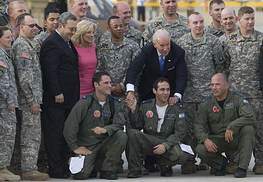 "U.S. Vice President Joseph Biden, center, Dr. Jill Biden, wearing a pink dress, and Israel's Defense Minister Ehud Barak, left of Jill Biden, pose for a snapshot with Golf 52nd aviation regiment based in Coleman army airfield Germany, and Israeli soldiers, bottom, at the Ben Gurion airport, near Tel Aviv, Israel, Thursday, March 11, 2010. Biden repeatedly voiced Washington's commitment to Israel's security, trying to allay any concerns it might have. But he also said an end to the conflict would restore to the Paelstinians ""the fundamental dignity and self-respect that their current predicament denies them."" Photo: Bernat Armangue, AP"