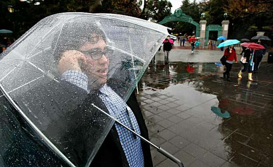 UC Berkeley freshman, Bryan Rahmanan, stops near Sather Gate on the Cal campus to make a phone call under the shelter of his umbrella during a down pour in Berkeley, Calif. on Friday Mar. 12, 2010. Photo: Michael Macor, The Chronicle